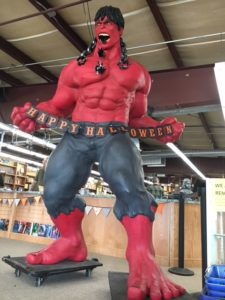 A towering red Incredible Hulk holds a Happy Halloween banner in front of bookshelves