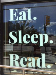 A bookstore window reflecting a city street with the words Eat. Sleep. Read. printed in big white letters.