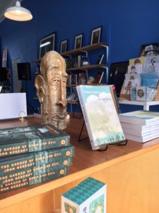 A stack of Midnight in the Garden of Good and Evil next to a stand displaying Truman Capote's In Cold Blood and a stone figurine of an elongated bald headed man