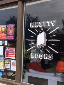 A window with Whitty Books logo and several flyers, with bookshelves and padded chairs visible through the window
