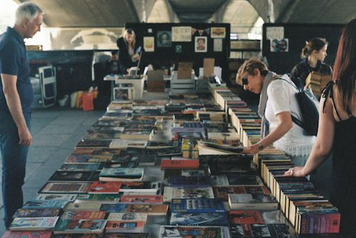 Photo of woman looking at books on a table
