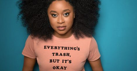 """Phoebe Robinson in a peach tshirt that says """"everything's trash, but it's okay"""""""