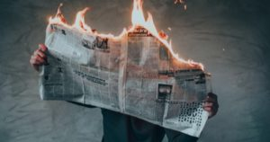 burning newspaper bad news feature