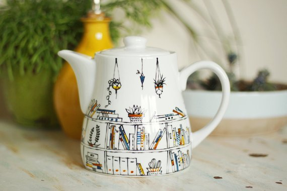 hand-painted porcelain teapot with bookshelves and hanging plants