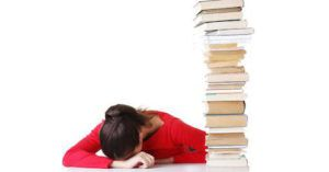 sad woman with head down next to book stack