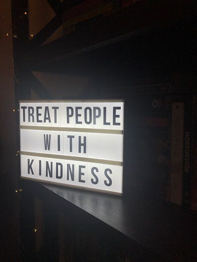 'treat people with kindness' quote on a light box