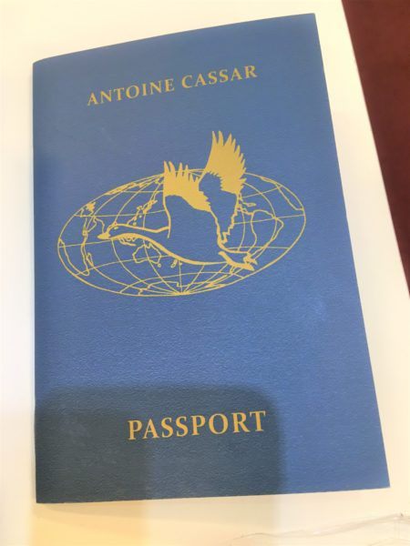 "A blue pamphlet resembling a passport, with the text ""Antoine Cassar"" and an image of a bird over a globe"