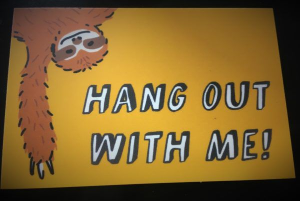 "A sloth hangs upside down, smiling. Text reads ""Hang out with me."""
