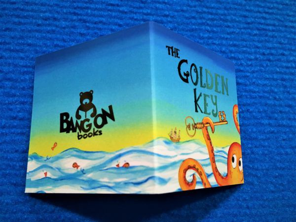 "A tiny folded business card, showing a cartoon-style octopus and ocean, with the text ""The Golden Key"" and ""Bangon Books"""