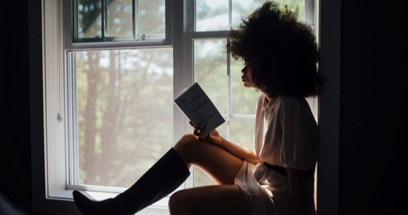 black woman reading in window home page feature