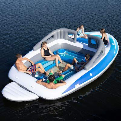 Image of people sitting in a beach float shaped like a speed boat.