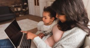 child and mother looking at a laptop feature