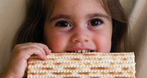 child eating matzah for Passover Judaism feature