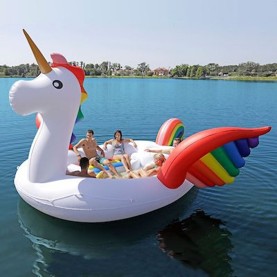 Image of people sitting in a giant unicorn-shaped beach float.