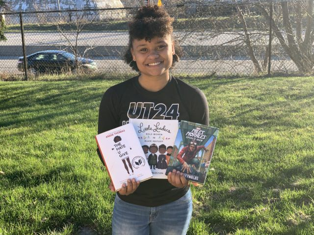 Nyesha Stone, with three books by authors of color. Photo used with permission of Stone.