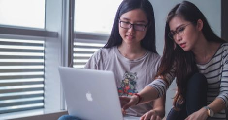 young women teen girls looking at laptop girls who code feature