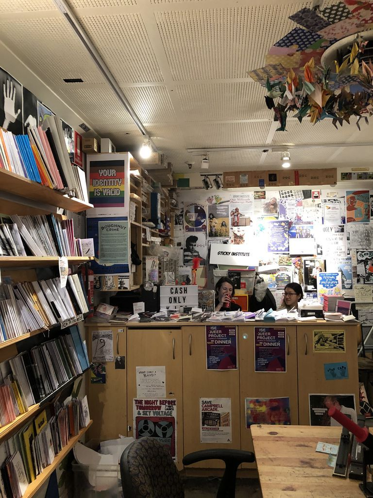Shop counter staffed by two women, surrounded by publications