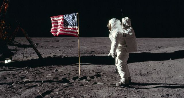 Astronaut Buzz Aldrin, Lunar Module pilot of the first lunar landing mission, poses for a photograph beside the deployed United States flag during an Apollo 11 Extravehicular Activity (EVA) on the lunar surface public domain