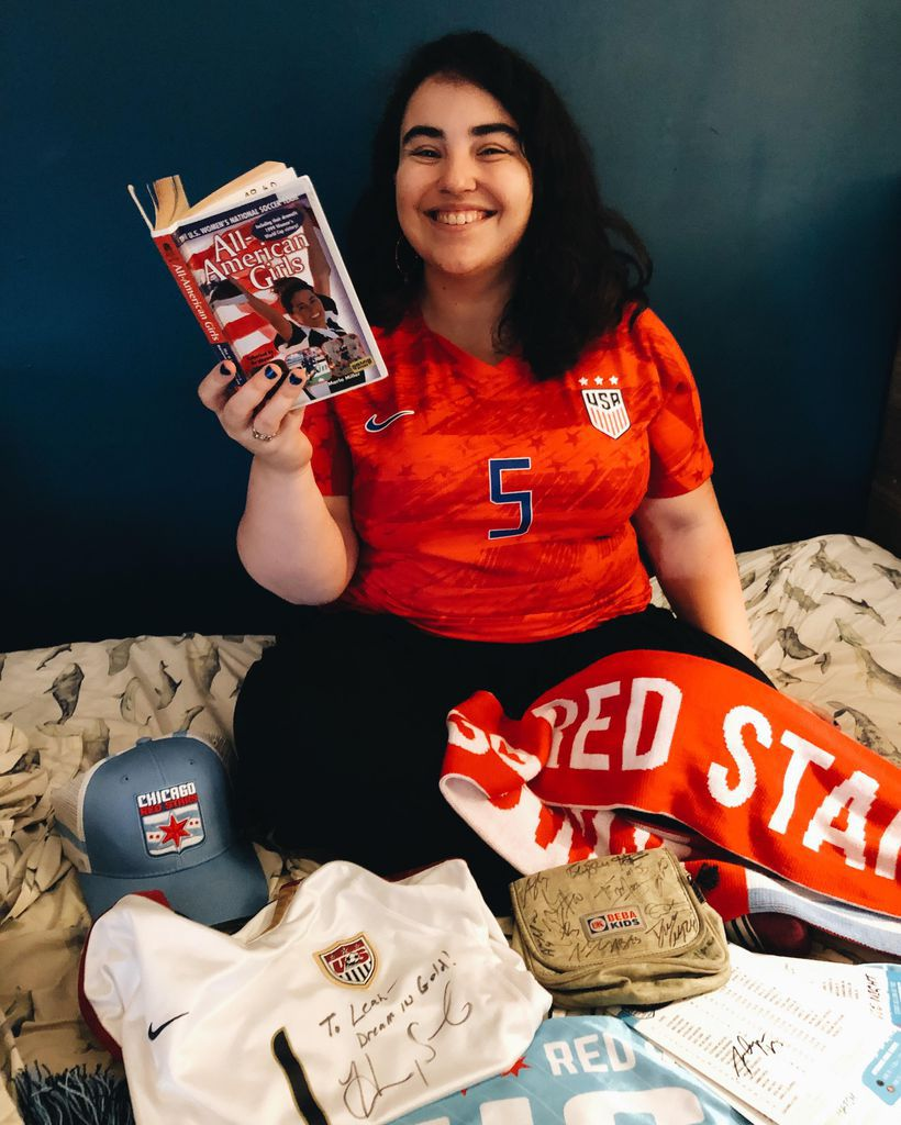 Brunette in a women's soccer jersey reading a book and surrounded by women's soccer gear