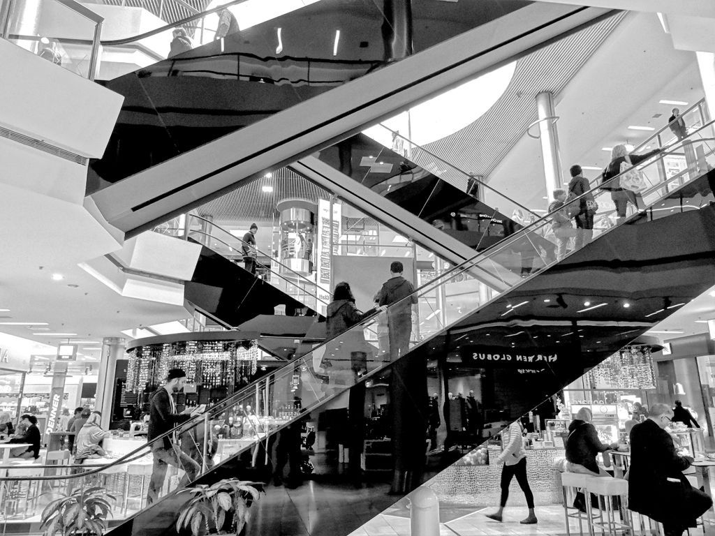 Black-and-white scene of people on escalators in a department store.