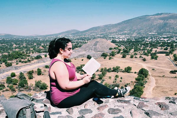 A woman sitting and reading a book with a pyramid in the background
