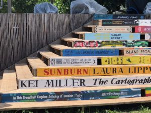 Stairway at the Calabash decorated with cover images and titles from featured books. Source: author.