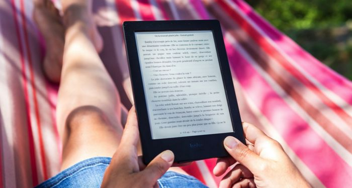 person in a striped hammock reading a story on a Kindle