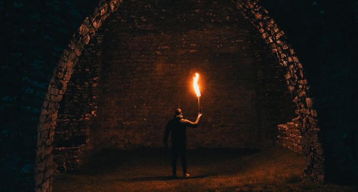image of a man holding a torch in cave ruins https://unsplash.com/photos/5DIFvVwe6wk