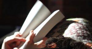 image of hands holding a book while resting on a blanket https://unsplash.com/photos/xZiHAa09Jcs