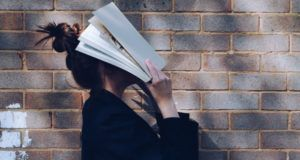 woman holding book over face