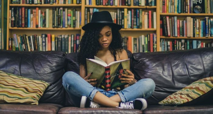 teen reading in front of a bookshelf