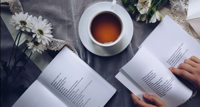 a cup of tea and flowers arranged next to two open books of poetry