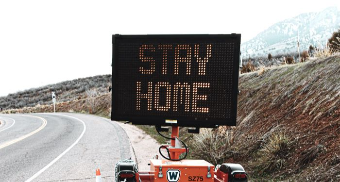 """image of sign on highway that reads '""""stay home"""" / https://unsplash.com/photos/MoQW0FhWPEk"""