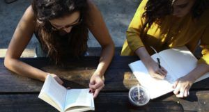 Image of people reading books outside together