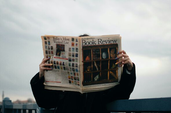 How to Write a Professional Book Review l BookRiot.com (Source: https://www.pexels.com/photo/person-holding-white-and-brown-newspaper-3957616/)