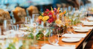 a long table set with glassware, white dinnerware, and flowers