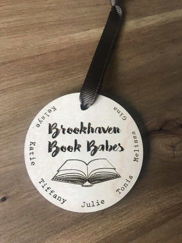 """Wood circle ornament with image of open book and """"brookhaven book babes"""" laser cut in the middle with names on the outside edges"""