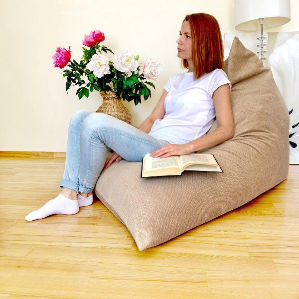 woman sitting with book in large tan triangle beanbag