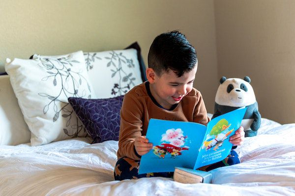 criança lendo na cama;  Foto de Unsplash: https://unsplash.com/photos/Y9RFMB7Gb94