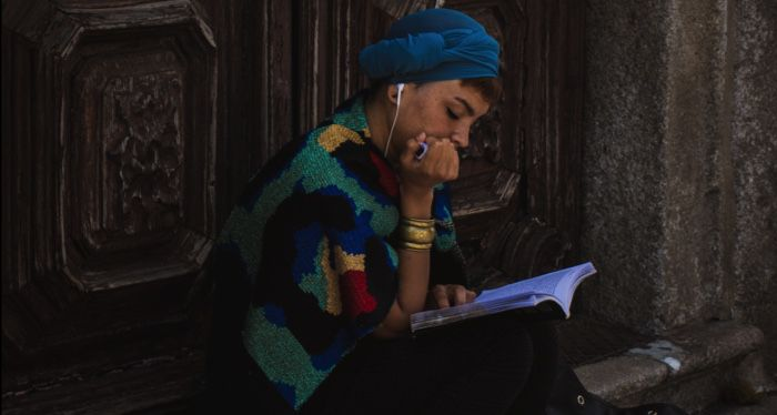 woman reading while listening to music on headphones
