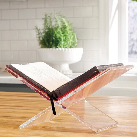 Clear, acrylic stand with an open book. Stand sits on a wooden table. Link: https://akamai-scene7.ballarddesigns.com/is/image/ballarddesigns/T_WithoutZoom?$w400$&$src=ballarddesigns/AS304_main