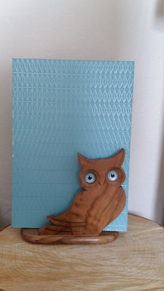 A book holder shaped like an owl sits on a desk. A blue book rests on the holder. Link: https://i.etsystatic.com/9184374/r/il/71ad29/1496295552/il_1140xN.1496295552_tdja.jpg