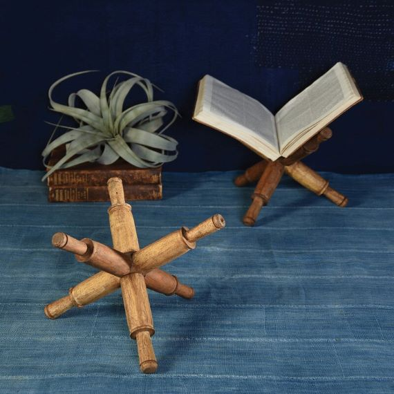 Two portable book stands shaped like jacks. A book sits on one of them. A small plant is in the background. Link: https://secure.img1-fg.wfcdn.com/im/26018860/resize-h800%5Ecompr-r85/9443/94435879/Library+Desktop+Book+Stand.jpg