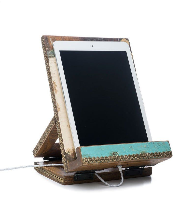 Wooden portable book stand. Oblong shaped. Teal edging. A tablet rests on the stand. Link: https://secure.img1-fg.wfcdn.com/im/01253702/resize-h800-w800%5Ecompr-r85/1156/115681429/Puri+Holder+Accessory.jpg