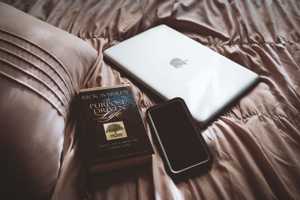 silver macbook beside black ipad on brown leather couch