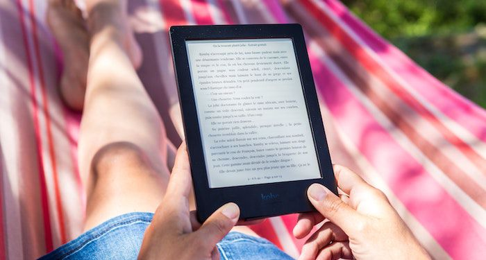 person in a striped hammock reading on an Amazon Kindle