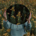woman holding mirror in field