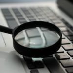 image of a magnifying glass being held over a laptop computer https://unsplash.com/photos/d9ILr-dbEdg