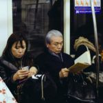 elderly woman reading on the subway