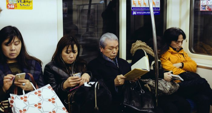 elderly woman reading on the subway